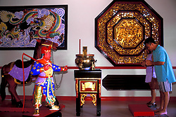 Stock photo of two People Bowing Inside the Texas Guandi Buddhist Temple
