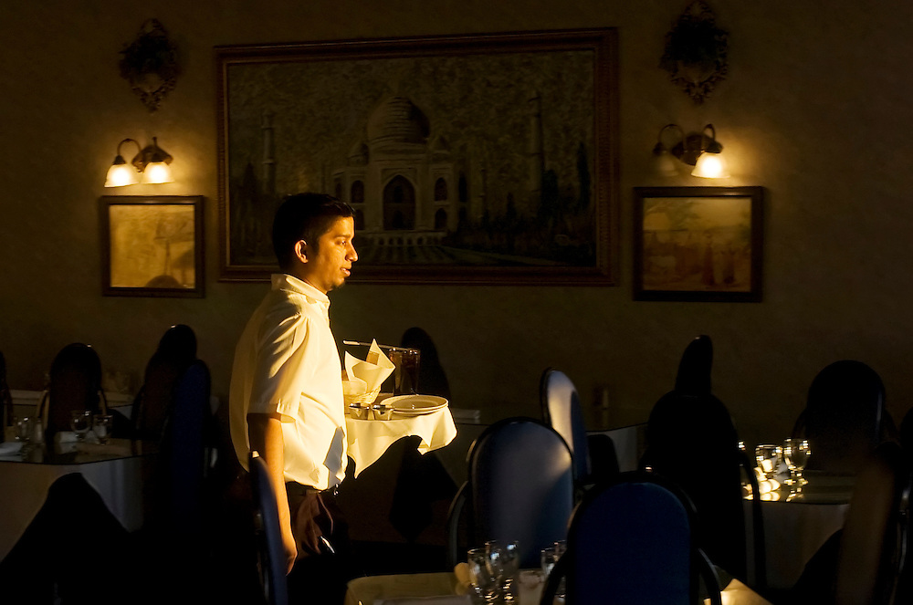 Matt Dixon | The Flint Journal..Joystan Dcosta brings drinks and bread to a table at Grill of India in Flint Township.
