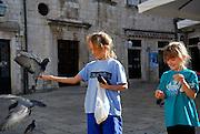 Two children (9 years old, 5 years old) feeding pigeons on Gunduliceva Poljana (Square), Dubrovnik old town, Croatia