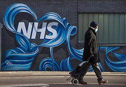 © Licensed to London News Pictures.21/01/2021, London, UK. People pass the NHS mural made by<br /> Rosie Woods in east London as the third national lockdown continues and hospitals are struggling to cope with the number of admissions. Photo credit: Marcin Nowak/LNP