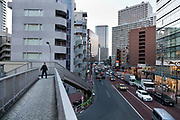 man on a pedestrian walking bridge in the Shibaura district Tokyo