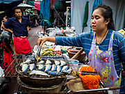 """18 MAY 2017 - BANGKOK, THAILAND: A woman grills fish on a street in Bangkok's Chinatown. City officials in Bangkok have taken steps to rein in street food vendors. The steps were originally reported as a """"ban"""" on street food, but after an uproar in local and international news outlets, city officials said street food vendors wouldn't be banned but would be regulated, undergo health inspections and be restricted to certain hours on major streets. On Yaowarat Road, in the heart of Bangkok's touristy Chinatown, the city has closed some traffic lanes to facilitate the vendors. But in other parts of the city, the vendors have been moved off of major streets and sidewalks.      PHOTO BY JACK KURTZ"""