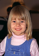Smiling girl age 4 in blue jumper.  Brooklyn Center  Minnesota USA