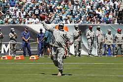 An Army serviceman throws a football on the field before the Philadelphia Eagles NFL football training camp practice in Philadelphia, Monday, August 5, 2013. (Photo by Brian Garfinkel)