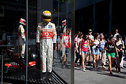 Area around Stratford in East London, home to the 2012 Olympic Games. People walking past a shop window showing Formula 1 driver suits as worn by the Maclaren team, at Westfield Shopping Centre.