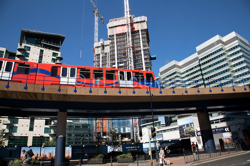DLR train on elevated tracks pulls past construction of new apartment buildings into the Canary Wharf financial district at South Quay in London, England, United Kingdom. Canary Wharf is a financial area which is still growing as construction of new skyscrapers continues. The Docklands Light Railway is an automated light metro system opened in 1987 to serve the redeveloped Docklands area of London.
