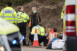 Enfield, UK. 15th September, 2021. Metropolitan Police officers arrest Insulate Britain climate activists who had blocked a slip road from the M25 at Junction 25 as part of a campaign intended to push the UK government to make significant legislative change to start lowering emissions. The activists, who wrote to Prime Minister Boris Johnson on 13th August, are demanding that the government immediately promises both to fully fund and ensure the insulation of all social housing in Britain by 2025 and to produce within four months a legally binding national plan to fully fund and ensure the full low-energy and low-carbon whole-house retrofit, with no externalised costs, of all homes in Britain by 2030 as part of a just transition to full decarbonisation of all parts of society and the economy.