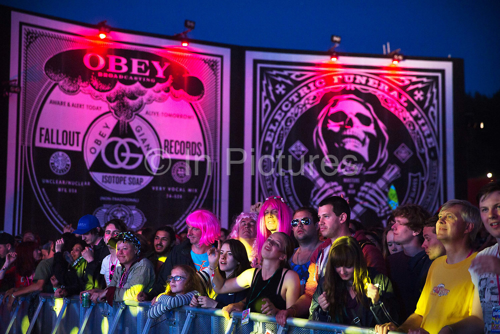 Dancing in front of Shepard Fairey Obey posters in the Hell arena, Shangri La field, Glastonbury Festival 2016. The Glastonbury Festival is the largest greenfield festival in the world, and is now attended by around 175,000 people. Its a five-day music festival that takes place near Pilton, Somerset, United Kingdom. In addition to contemporary music, the festival hosts dance, comedy, theatre, circus, cabaret, and other arts. Held at Worthy Farm in Pilton, leading pop and rock artists have headlined, alongside thousands of others appearing on smaller stages and performance areas.