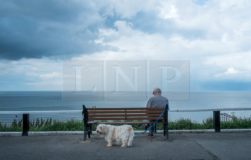 © Licensed to London News Pictures. <br /> 06/08/2014. <br /> <br /> Saltburn by the Sea, United Kingdom<br /> <br /> A man sits with his dog on the upper promenade in Saltburn by the Sea in Cleveland as storm clouds build further out in the North sea.<br /> <br /> Photo credit : Ian Forsyth/LNP