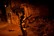 "In this Aug. 11, 2012 photo, a trafficker test fires a riffle in the Mandela slum in Rio de Janeiro, Brazil. <br /> <br />  The South American country began experiencing a public health emergency in recent years as demand for crack boomed and open-air ""cracolandias,"" or crack lands, popped up in the sprawling urban centers of Rio and Sao Paulo, with hundreds of users gathering to smoke the drug. The federal government announced in early 2012 that more than $2 billion would be spent to fight the epidemic, with the money spent to train local health care workers, purchase thousands of hospital and shelter beds for emergency treatment, and create transitional centers for recovering users."