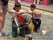 "Two boys prepare accordions to busk in a street fair in San Telmo (""Saint Pedro González Telmo""), the oldest historic neighborhood (barrio) in the heart of Buenos Aires, Argentina, South America."