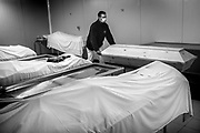A mortuary employee, wearing protective gear, prepares coffins during the coronavirus disease (COVID-19) outbreak, at the Saint-Pierre University Hospital, Brussels April 27, 2020.