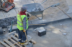 August 28, 2017 - Ankara, Turkey - A construction worker is pictured from above as he places concrete paving stones to build up a new pavement in the Kizilay square of Ankara, Turkey on August 28, 2017. (Credit Image: © Altan Gocher/NurPhoto via ZUMA Press)