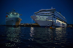© Licensed to London News Pictures.  12/06/2021. Falmouth, UK. Extinction Rebellion activists gather around Silja Europa cruise ship to project messages spreading swerves about shipping industry in Falmouth, Cornwall; on the second day of the G7. Photo credit: Marcin Nowak/LNP
