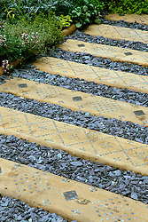 Path with slate chippings and wooden sleepers. Galvanised nails punched into lead for decoration. Design: David Rosewarne and Magie Gray