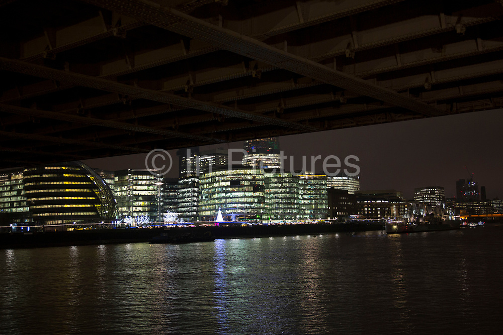 View at night looking towards More London and it's architecture from underneath the riveted structure of Tower Bridge in London, England, United Kingdom.