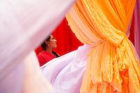 Inde, Rajasthan, Usine de Sari, Les tissus sechent en plein air. Ramassage des tissus secs par Dimpel, 15 ans,  avant le repassage. Les tissus pendent sur des barres de bambou. Les rouleaux de tissus mesurent environ 800 m de long. <br />  // India, Rajasthan, Sari Factory, Textile are dried in the open air. Collecting of dry textile  are folded by Dimpel, 15 years old. The textiles are hung to dry on bamboo rods. The long bands of textiles are about 800 metre in length.