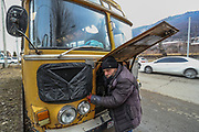 A bus driver is seen working in the engine of an old Soviet passenger bus that is parked at the entry of Vanadzor city on Sunday, Jan 16, 2021. Vanadzor is the third-largest city in Armenia, serving as the capital of Lori Province in the northern part of the country. It is located about 128 kilometres north of the capital Yerevan. (Photo/ Vudi Xhymshiti)