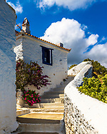 House with white walls and blue window shutters in Skopleos island