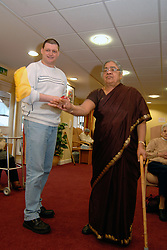 A Care Assistant helps an elderly Sikh lady to play a game with bean bags;  in a day centre; Bradford,