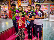 "29 MARCH 2017 - BANG KRUAI, NONTHABURI, THAILAND:  A family stands in the family sized coffin before their ritualistic death at Wat Ta Kien (also spelled Wat Tahkian), a Buddhist temple in the suburbs of Bangkok. People go to the temple to participate in a ""Resurrection Ceremony."" Groups of people meet and pray with the temple's Buddhist monks. Then they lie in coffins, the monks pull a pink sheet over them, symbolizing their ritualistic death. The sheet is then pulled back, and people sit up in the coffin, symbolizing their ritualist rebirth. The ceremony is supposed to expunge bad karma and bad luck from a person's life and also get people used to the idea of the inevitability of death. Most times, one person lays in one coffin, but there is family sized coffin that can accommodate up to six people. The temple has been doing the resurrection ceremonies for about nine years.         PHOTO BY JACK KURTZ"