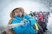 Large group of workers holding rope during snowfall, Nozawaonsen, Japan