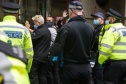 Activists from HS2 Rebellion, an umbrella campaign group comprising longstanding campaigners against the HS2 high-speed rail link as well as Extinction Rebellion activists, are pictured glued to the doors of the Department for Transport during a protest on 4 September 2020 in London, United Kingdom. Activists glued themselves to the doors and pavement outside the building and sprayed fake blood around the entrance during a protest which coincided with an announcement by HS2 Ltd that construction of the controversial £106bn high-speed rail link will now commence.