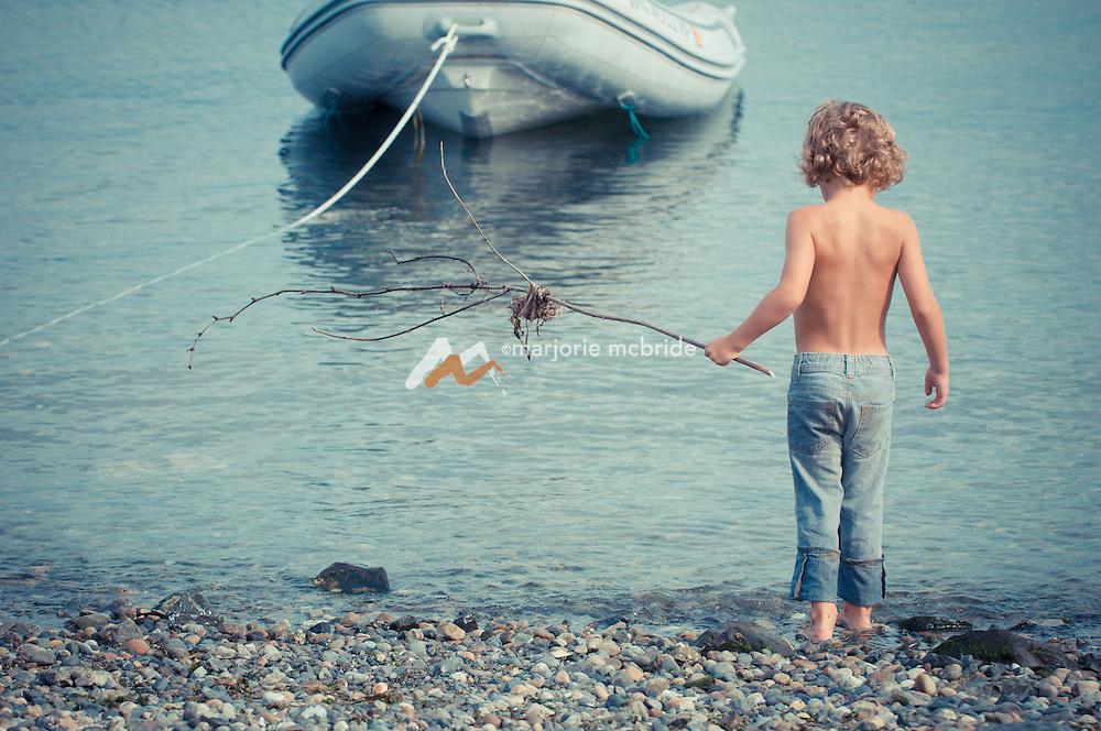 Cute little shirtless boy standing along the beach, Lummi Island, WA