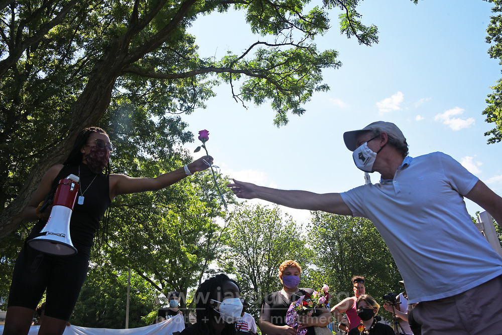 """Organizer Clark Atkinson honors victims at the event. Determined to keep continuing racial injustice in the public eye, a small but well-organized group of protesters held a July 4th """" March for Liberty and Justice for All"""" in Waterbury, CT,  gracing each individual murdered with roses in an urgent, emotional appeal. Photograph by Jay Dunn."""