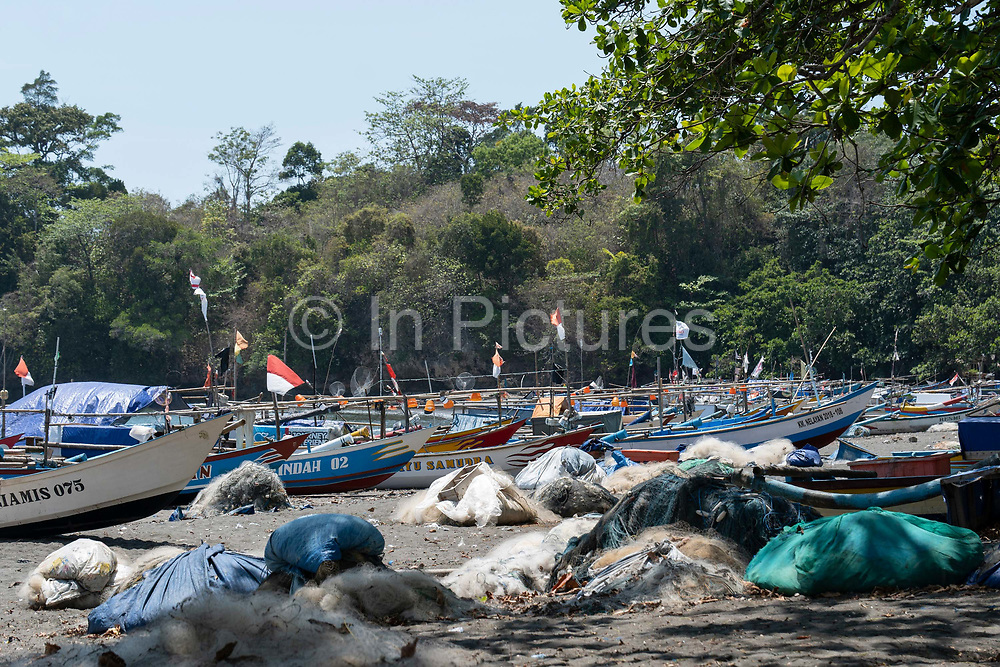 Traditional wooden fishing boats line the beach at Batu Karas on the 31st October 2019 in Java in Indonesia.