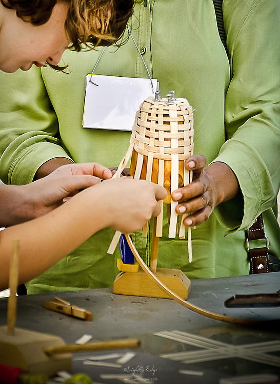 A young attendee to the Wheaton Arts Fine Craft Festival has a go at making a small basket.