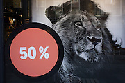 Image of a lion with a fifty percent (50%) reduction off prints, displayed outside a central London retailer.