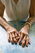 Huong Phung rests her 92 year old hands after making paper clothes to burn for prayer at the Chua Dieu Vien Pagoda, Hue, Vietnam.  The Chua Dieu Vien Pagoda houses 25 elderly women whose families left their rural homes to seek employment in urban areas.  Photo by Stan Olszewski/SOSKIphoto