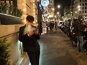 Man vaping whilc looking at his smartphone,  London 11 April 2019
