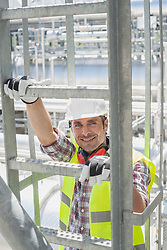 Portrait of an engineer climbing ladder at geothermal power station, Bavaria, Germany