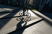 While office workers remain at home in accordance to government Covid guidelines and individual corporate policies, a cyclist rides through sunlight during a quieter rush-hour in the City of London, the capital's financial district, during the third lockdown of the Coronavirus pandemic, on 9th March 2021, in London, England.