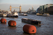 View of barges and boats on the River Thames looking towards Tower Bridge in London, England, United Kingdom.