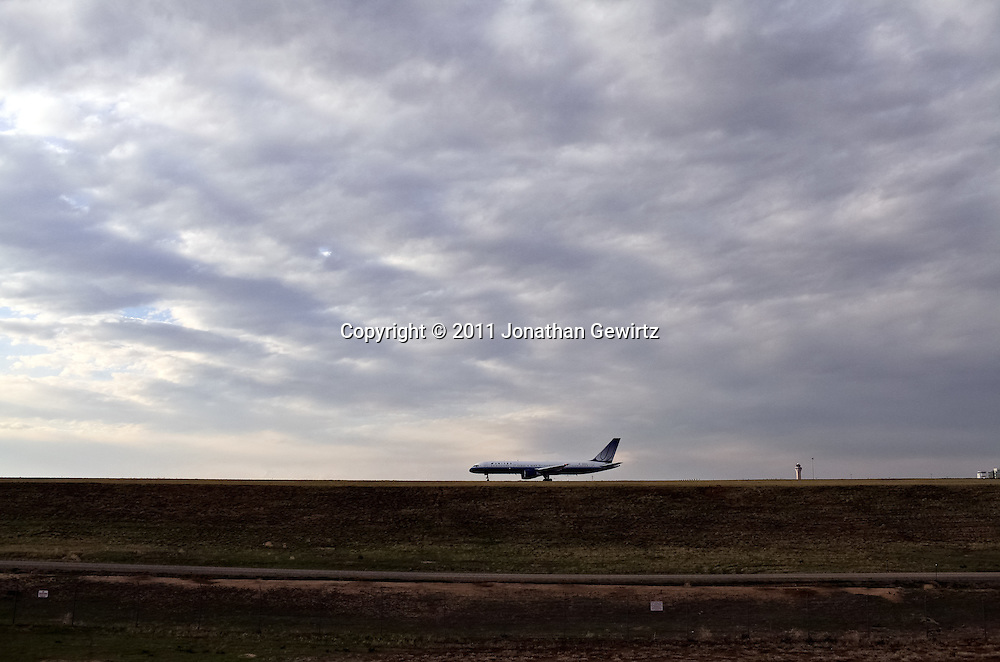 A United Airlines Boeing jetliner on the taxiway at Denver International Airport is silhouetted against a cloudy sky. WATERMARKS WILL NOT APPEAR ON PRINTS OR LICENSED IMAGES.