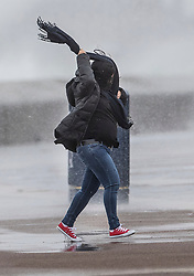 © Licensed to London News Pictures. 08/02/2019. Southsea, UK. A woman struggles with her scarf as waves crash against the sea wall at Southsea, near Portsmouth. Storm Erik is hitting southern parts of the UK. Photo credit: Peter Macdiarmid/LNP