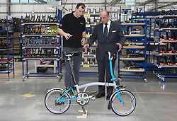 The Duke of Edinburgh is shown a Brompton bicycle by the company's CEO Will Butler-Adams as he opens its new factory in Greenford, London.