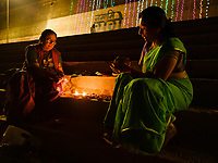 Varanasi, INDIA - CIRCA NOVEMBER 2018: Indian women lighting candles during Dev Deepawali, celebration in Varanasi . Varanasi is the spiritual capital of India, the holiest of the seven sacred cities and with that many rituals and offerings are performed daily by priests and hindus.