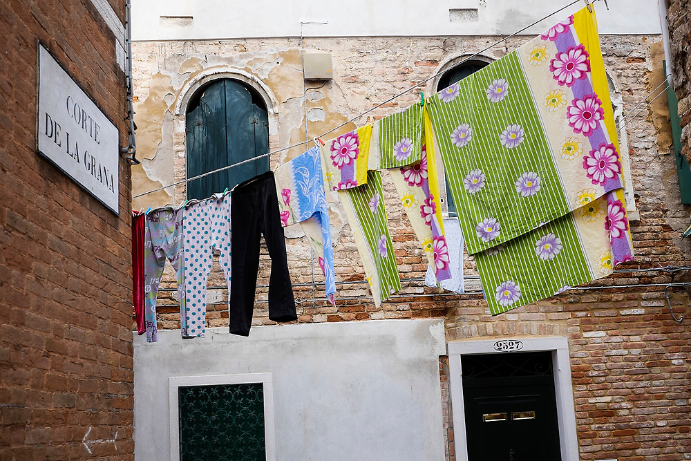 Drying clothes hanging out to dry on a washing line across a street on washday in Venice, Italy