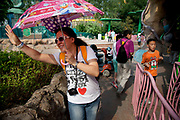 Woman with an umbrella waving to her friends. Happy Valley Beijing is an amusement park in Beijing, China built and operated by Beijing OTC, which is part of the Shenzhen OCT Holding Group. The park, which is located in the east of Beijing, opened in July, 2006. It is one of four theme parks in the brand chain. Similar in style with the Disney land park, Happy Valley Beijing also featured distinctive landscapes and themes throughout the resort along with featured rides within the different themes. In total there are more than 40 rides.