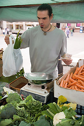 Stallholder serving fresh local produce on a stall at an outdoor Farmer's market,