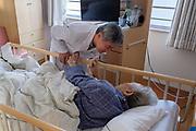 Makoto Hirakata, vice-president of Aiwa Hospice talks to his bedridden patient during the round check on November 16th, 2019 at Aiwa Hospice in Nagano, Japan.