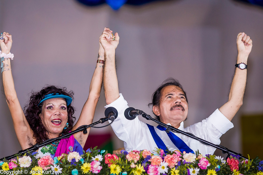 """10 JANUARY 2007 - MANAGUA, NICARAGUA:  ROSARIO MURILLO and her husband, DANIEL ORTEGA, President of Nicaragua, clasp hands during Ortega's inaugural speech in Managua. Ortega, the leader of the Sandanista Front, was sworn in as the President of Nicaragua Wednesday. Ortega and the Sandanistas ruled Nicaragua from their victory of """"Tacho"""" Somoza in 1979 until their defeat by Violetta Chamorro in the 1990 election.  Photo by Jack Kurtz"""