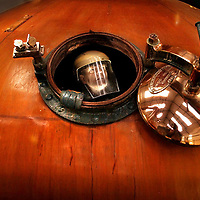 Production officer Mike Casey investigates inside a copper pot whisky still one of two stills producing 1.3 million litres annually,the pots have been emptyed of their contence to be cleaned before a new batch of Malt whisky is made at the Glenkinchie distillery in  East Lothian.Photograph David Cheskin./Press Association