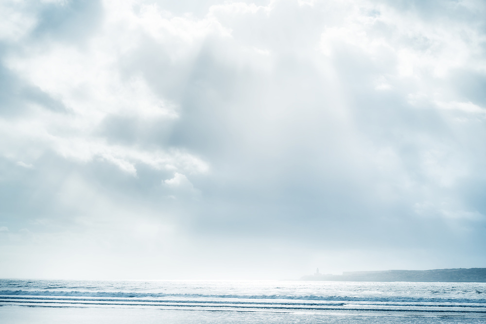 Beach and sea with cloudy sky and sunbeams. High key, soft effect image.