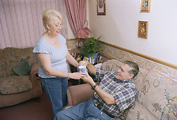 Wife giving man with Alzheimer's disease a cup of tea,