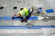 Richard Lamb lays down lane marker tiles in the warming pool at Milpitas High School in Milpitas, California, on July 18, 2014. (Stan Olszewski/SOSKIphoto)